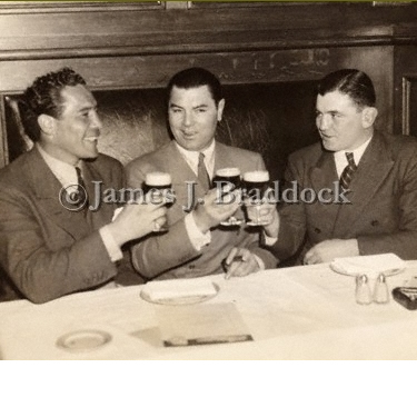 Max Baer, Jack Dempsey and Jim Braddock toast each other at Dempsey's restaurant in NYC, 1935