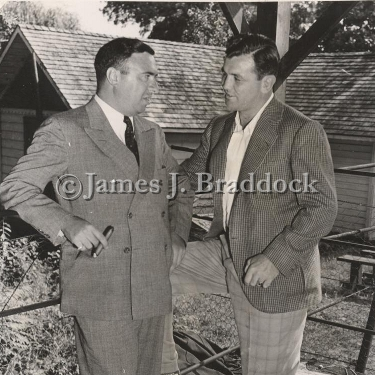 Abe Greene, boxing commissioner of New Jersey, and Jim Braddock at Joe Louis' training camp while Louis trains for the Tommy Farr fight. Pompton Lakes, NJ. 8/4/1937.