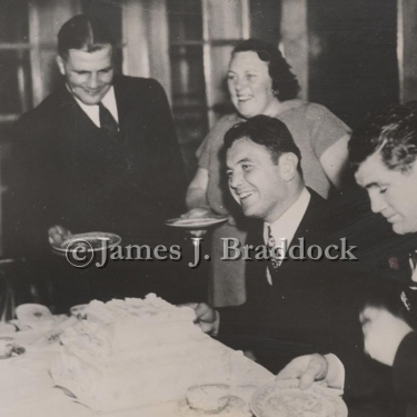 Jim and his sparring partner, Jack McCarthy(right), take a break from training for the Louis fight to enjoy some cake at the home of Mr. and Mrs. Karl Ogren. Lake Shishebogama in northern Wisconsin. 4/6/1937.