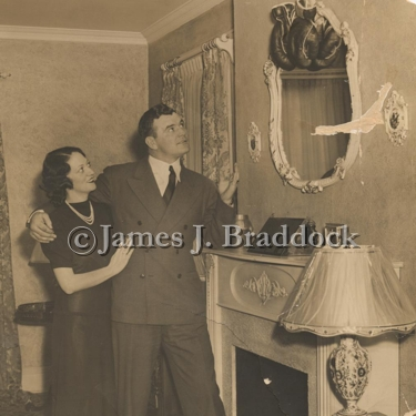 Mae & Jim Braddock look at a pair of the Champ's boxing gloves hanging over the fireplace in their North Bergen home.