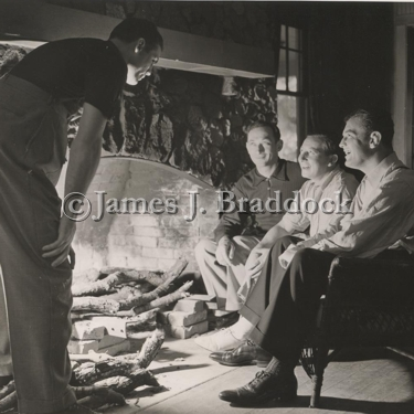 Sparring partner Jack McCarthy, Trainer Doc. Robb, Manager Joe Gould, and Jim Braddock keeping warm by the fire. Camp Kenosha, Wiss. 6/20/1937.